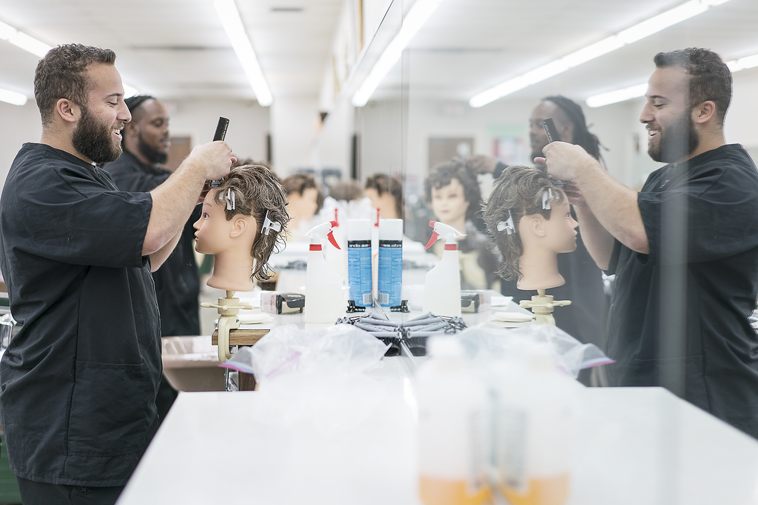 Flint, MI - Tuesday, February 6, 2018: Junior barbers Cole Stomp, 19, from Davison, and Tony Atlas, 32, from Flint practice on mannequins at the Flint Institute of Barbering.