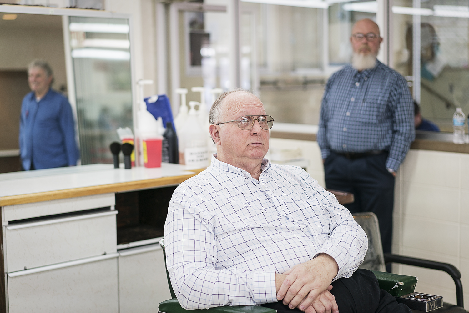 Flint, MI - Tuesday, February 6, 2018: Linden resident Larry Woodby, 70, an instructor at the Flint Institute of Barbering, sits in an empty chair flanked by the reflection of Bob Morey, 68, from Linden, Director of Education (left) and Ted Taylor, 66, from Flint Twp., (right), another of four instructors at the institute.Tim Galloway for FlintSide