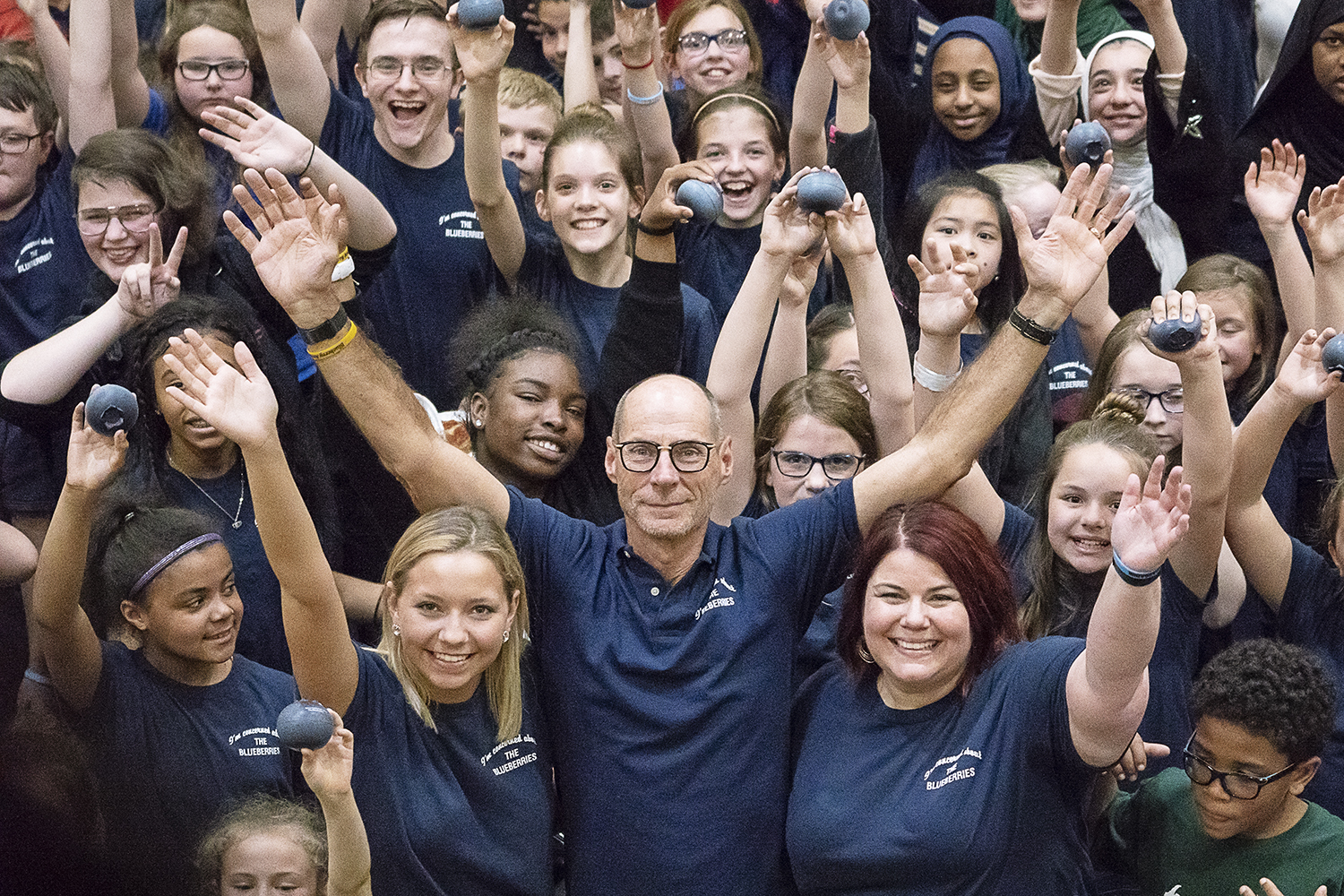 Flint, MI - Friday, May 4, 2018: Fenton Twp. resident and Blueberry Founder Phil Shaltz (center), 69, University of Michigan - Flint student Carryn White (left), 19, from Burton and FlintSide publisher Marjory Raymer (right), 44, from Flint, hold their hands up alongside the Blueberry Ambassadors for a group photograph after the 5th Annual Blueberry Ambassador Awards Party at the Riverfront Banquet Center downtown.