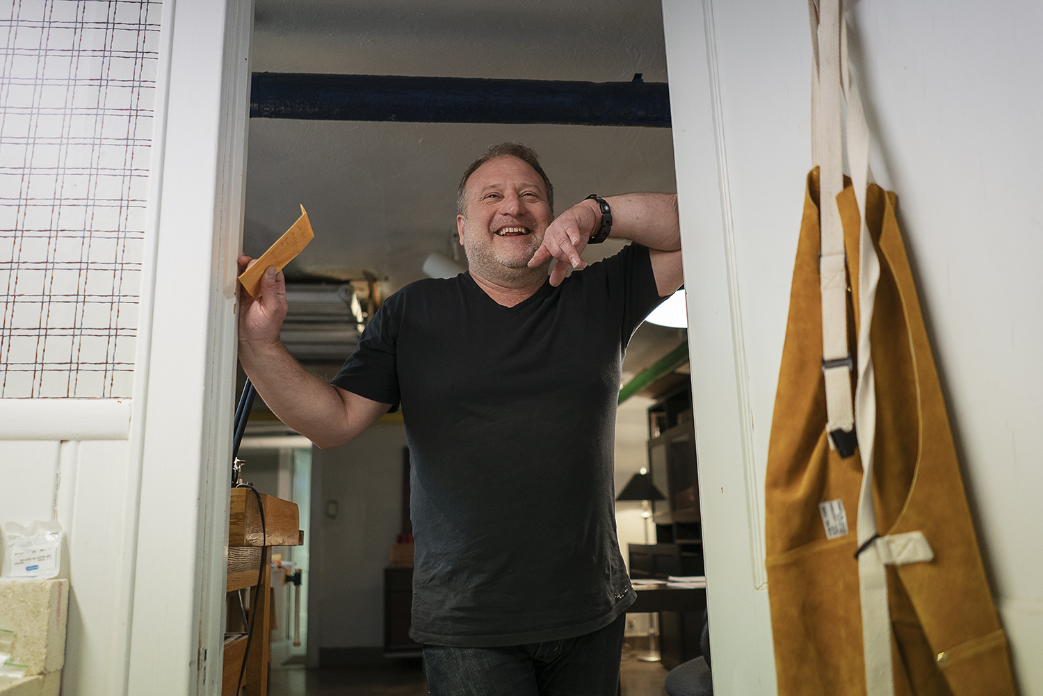 Flint, MI - Tuesday, May 8, 2018: Flint resident and metalsmith Robert McAdow laughs as he leans on the doorway to his soldering area in his studio.Tim Galloway for FlintSide