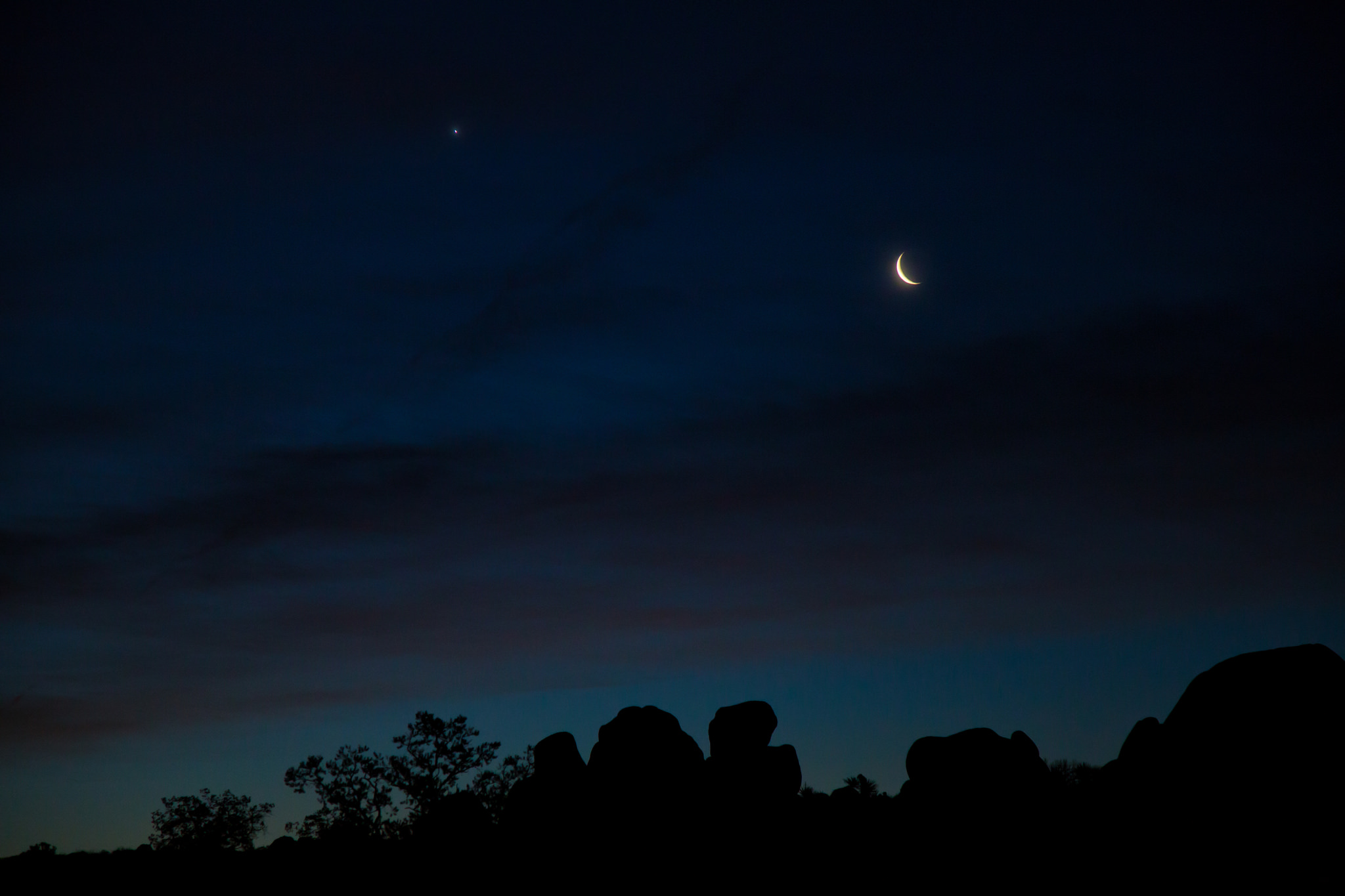 A waning crescent moon with planet Venus to the left just before sunrise at Skull Rock