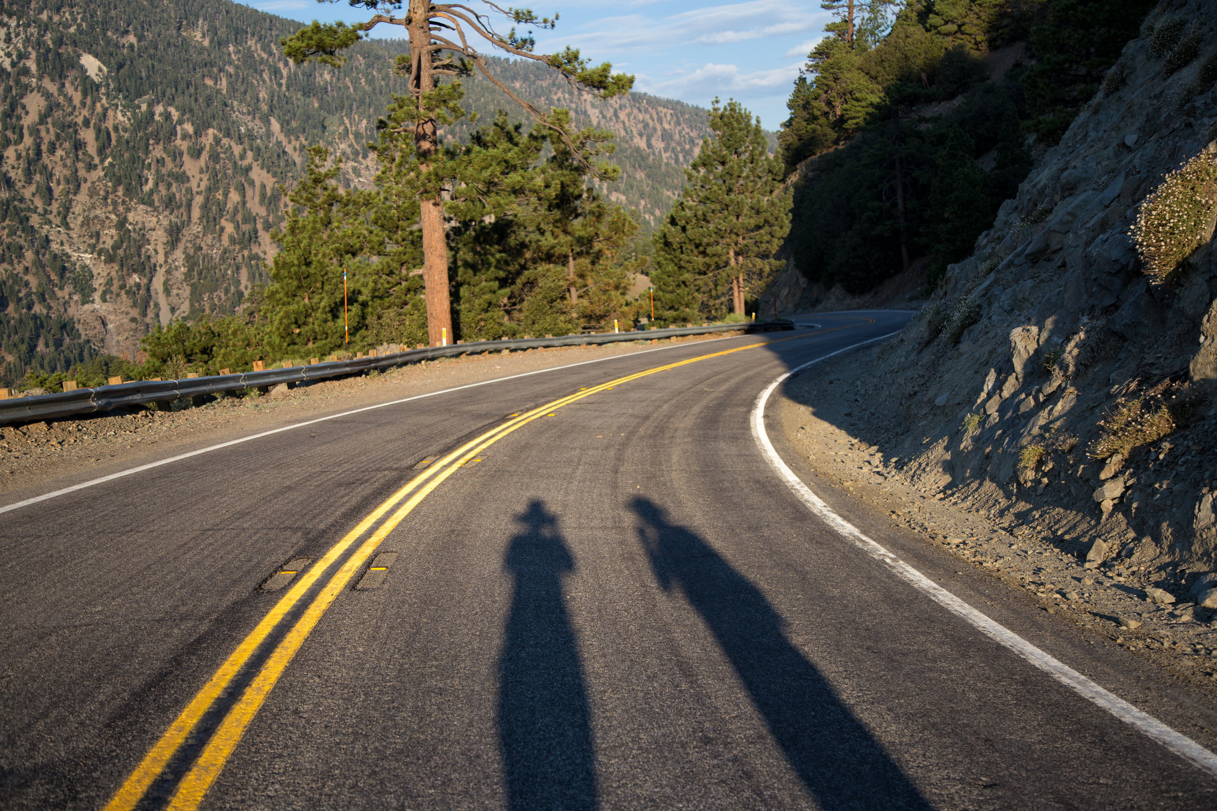 Our shadows as we walked down Highway 2 in the morning sunlight to the trailhead.
