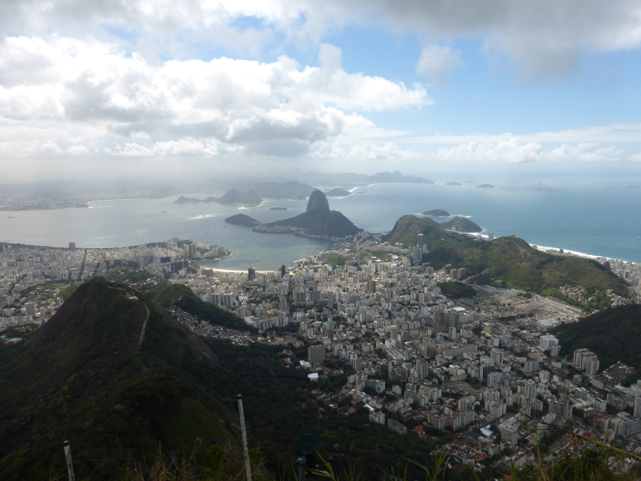This the view from the Redeemer of Sugarloaf mountain in the distance and a section of Rio. Because of the height of the peaks surrounding it, Rio was built in the valleys in between.
