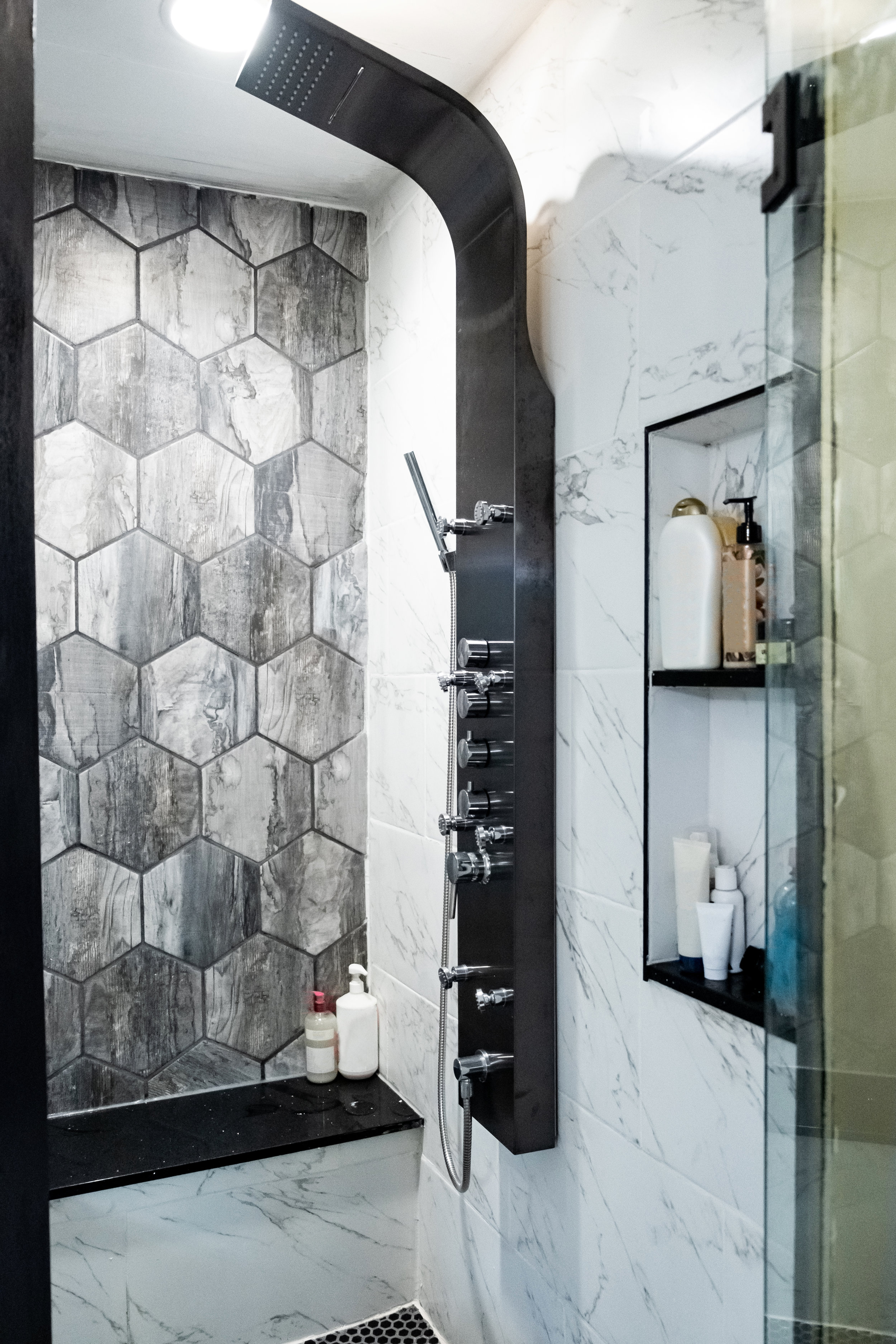 bathroom renovation, remodel, upgrade, modern, black and white, white marble tile, shower unit, cubby, shampoors, conditioner, bathroom