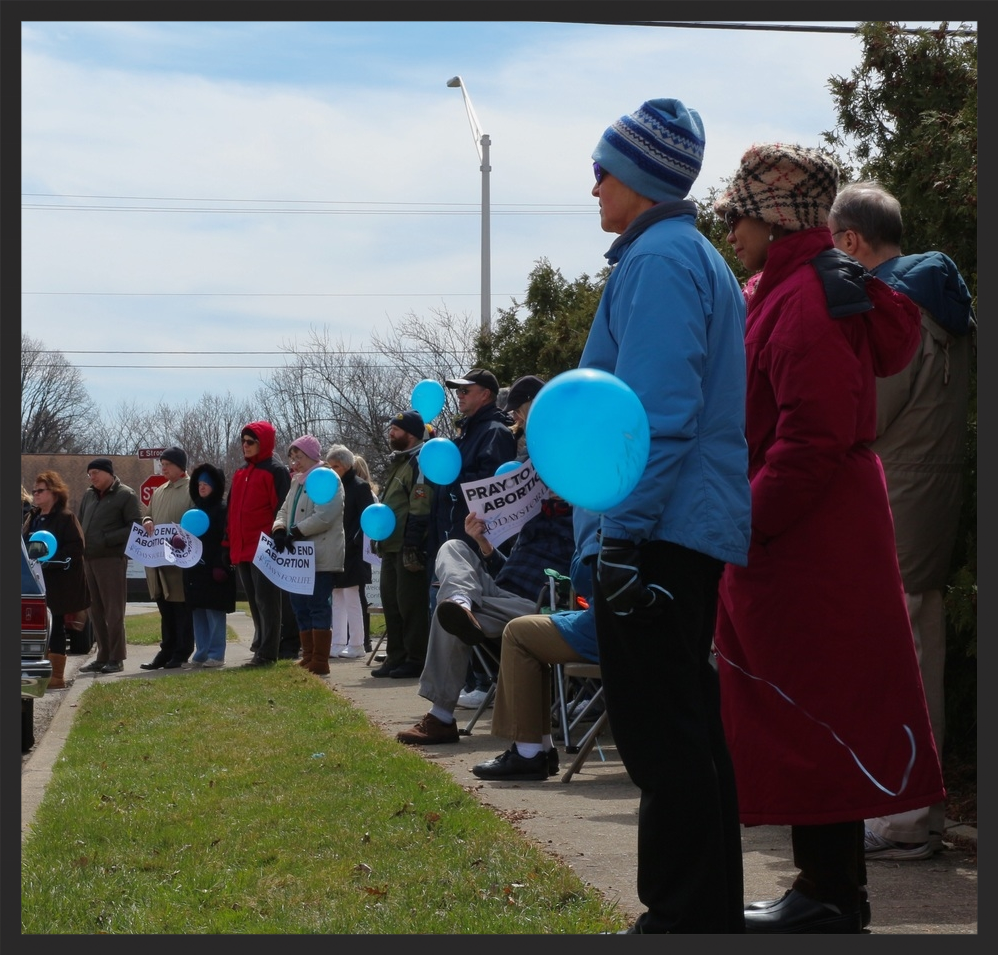 40 Days for Life protesters stand with balloons in hand as Mike Spencer with Life Training Institute delivers a message. Helium Balloons were said to signify remembrance for past abortions at Dr. Haskell's clinic.