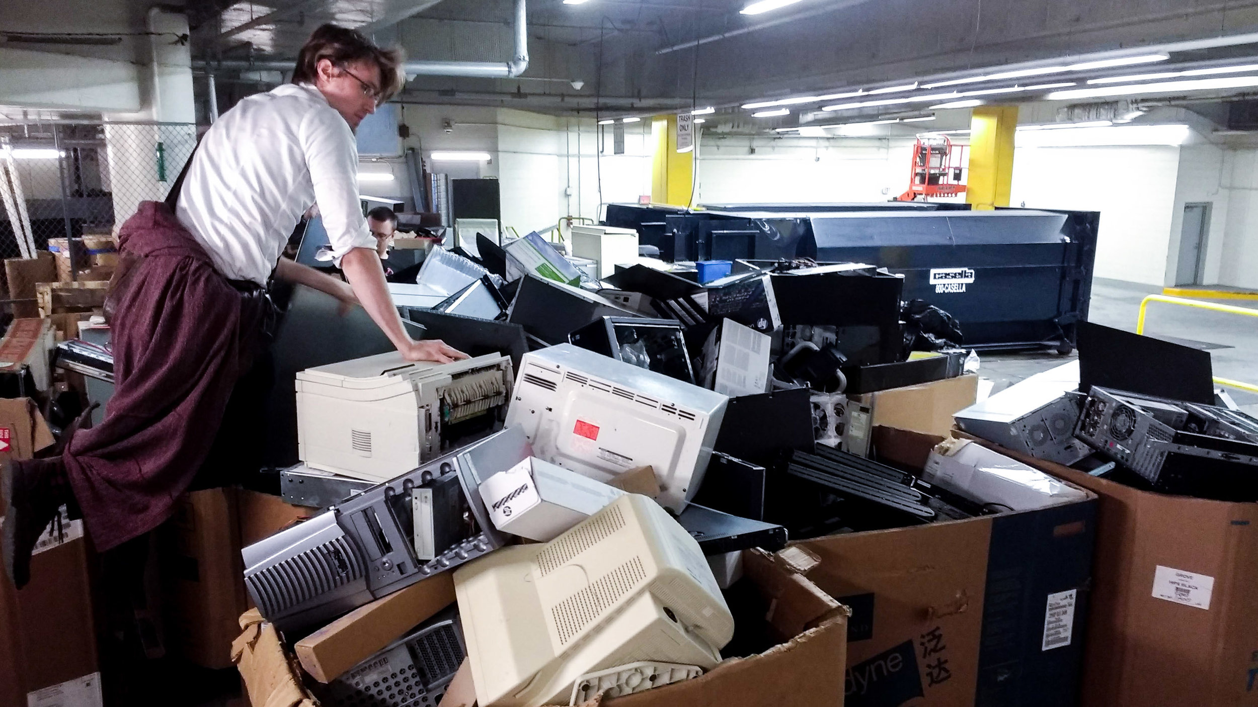Max looks for lab equipment in a pile of discarded electronics in Cambridge, Massachusetts.