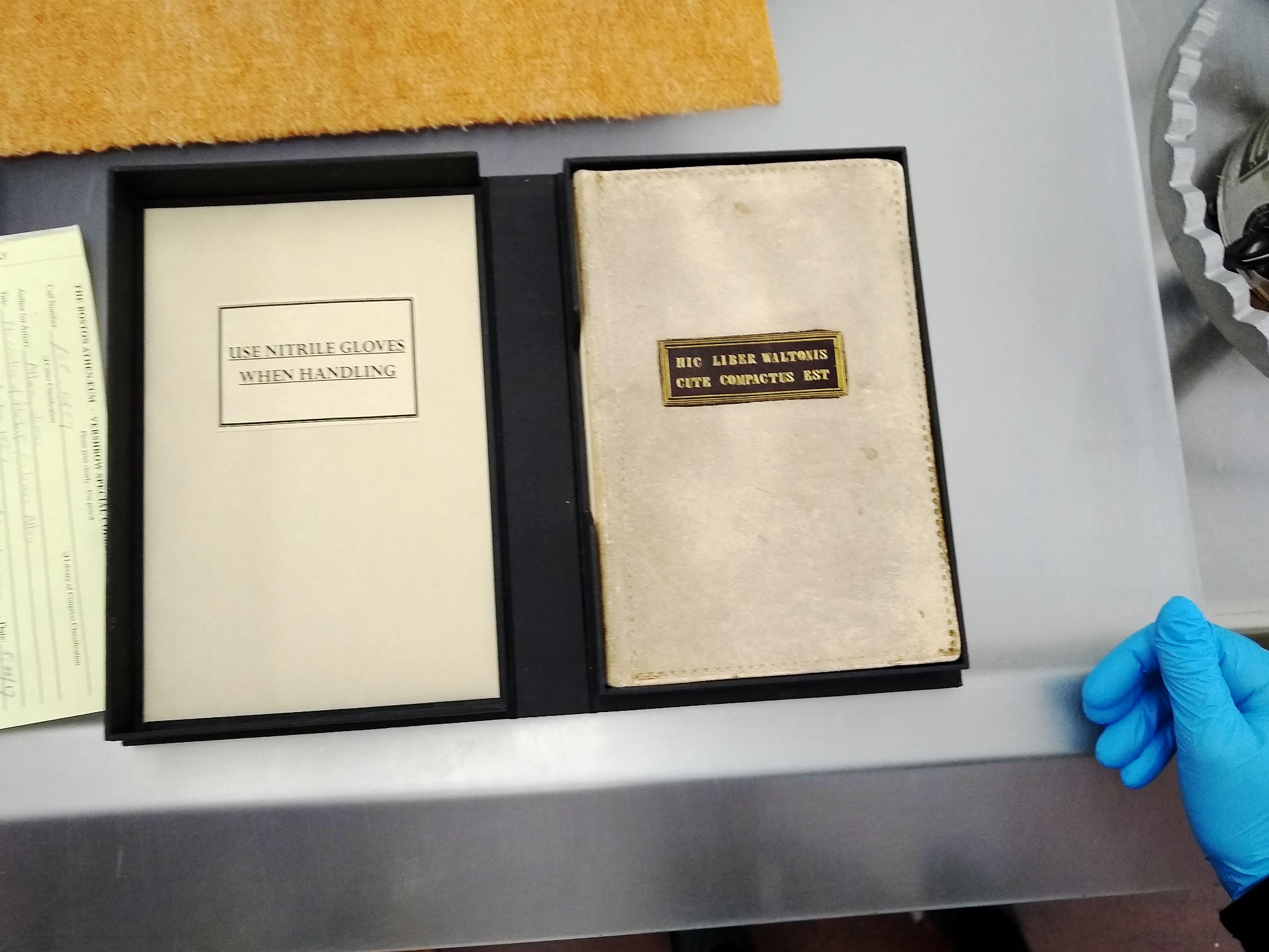 """The cover of James Allen's book, which states in Latin that the book has been bound in """"Walton's"""" skin, where """"Walton"""" was a pseudonym used by Allen. Also a warning to wear gloves while handling the book, as the binding may contain residual arsenic or other dangerous substances from the tanning process."""