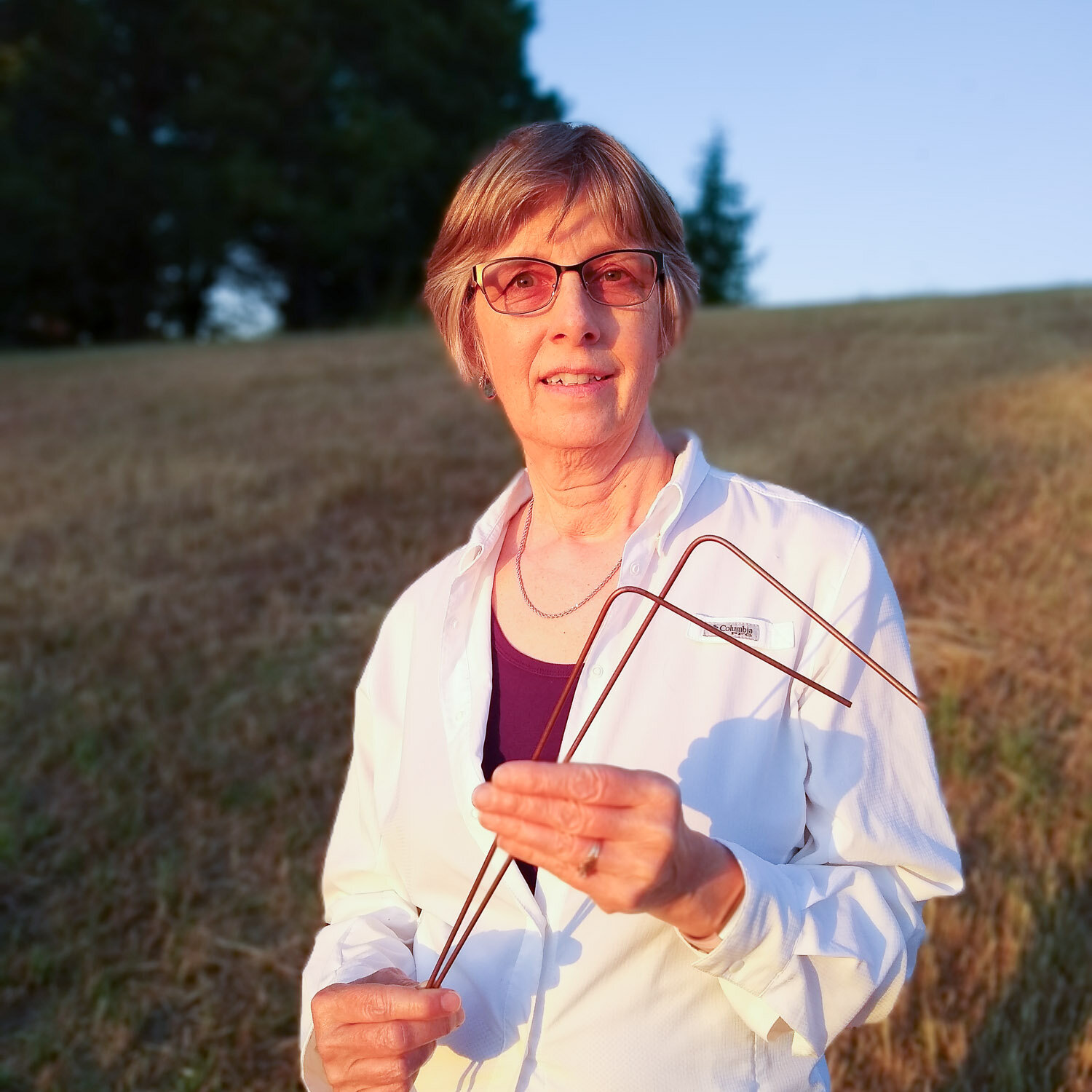 Kathy Emtman holding a the witching rods that her husband made for her in the nineties.