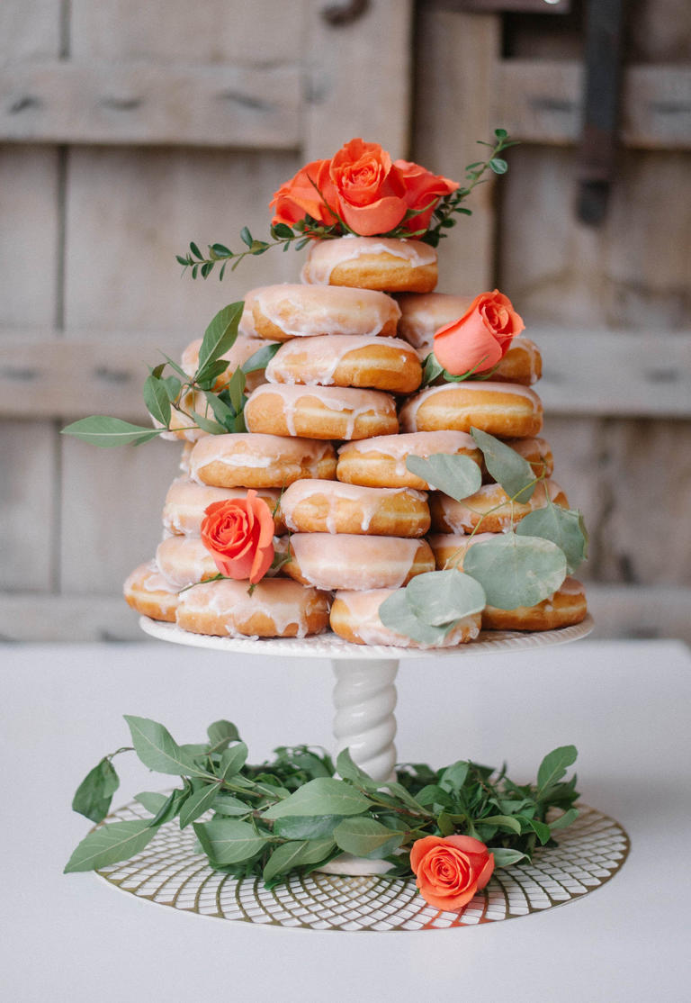 Orange roses and eucalyptus give this donut cake the perfect pop of color