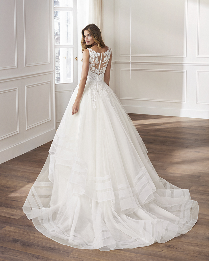 Lace and tulle princess-style wedding dress. V-neckline, embroidered bodice of beaded lace and ruffled tulle skirt