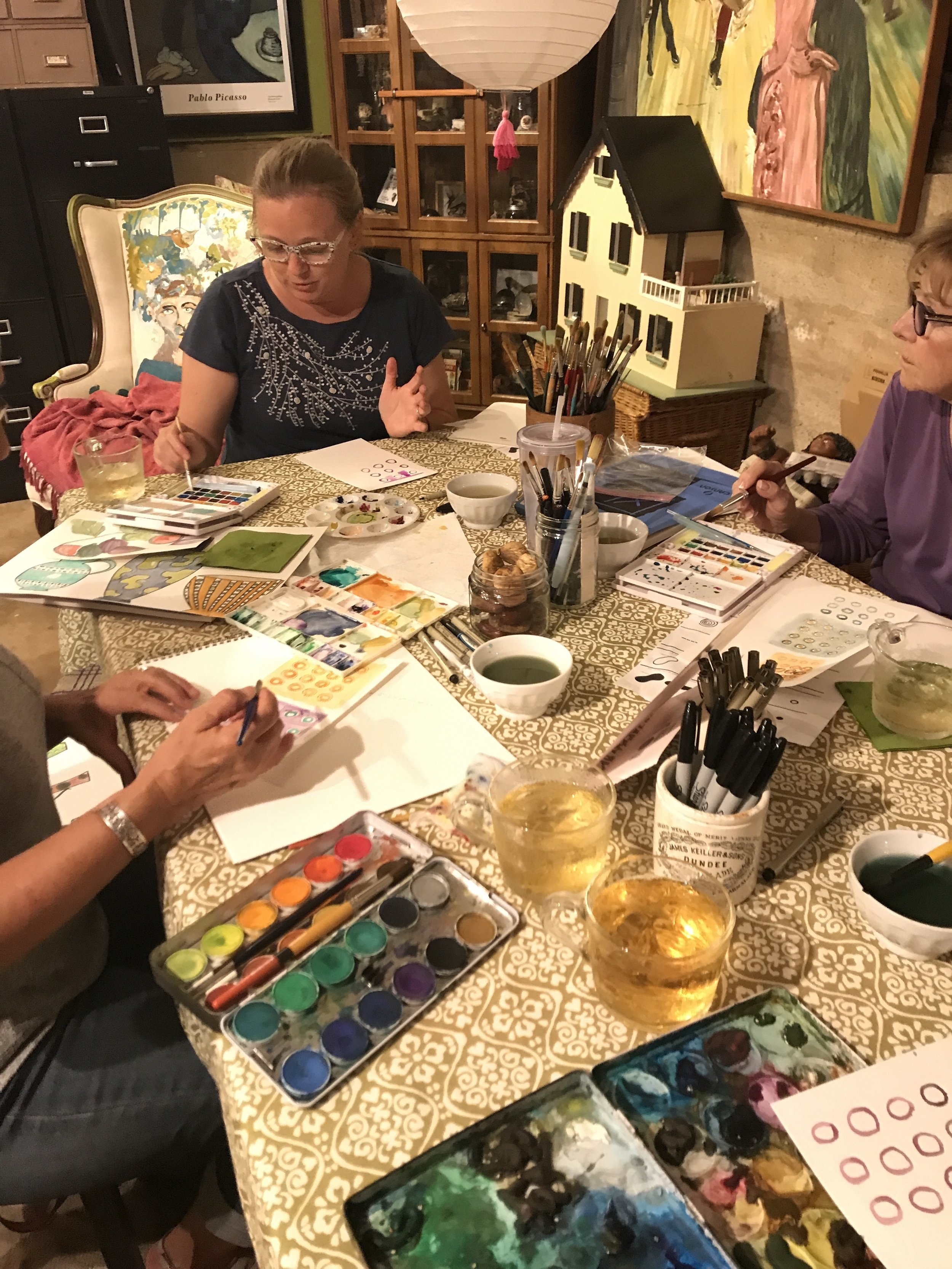 THE TABLE DURING AN OPEN STUDIO...WHERE SO MANY DIFFERENT TYPES OF WOMEN COME TO SIT AND PAINT. WE ARE FROM A VARIETY OF BACKGROUNDS AND FAMILIAL SITUATIONS. ALMOST ALL OF US HAVE A MEASURE OF HESITATION IN OUR CREATIVE PROCESS THAT HAS HELD US BACK FROM GOOD CREATIVE WORK. THE DIALOGUE IS RICH AT THIS WORK TABLE...AND FRIENDSHIPS BEGIN TO RUN DEEP EVEN IN THE FIRST FEW MONTHS OF GATHERING. IT IS EASY TO SIT QUIETLY FOR THE ENTIRE TIME, OR TO WALK THROUGH THE STUDIO DOORS WITH A TOPIC YOU'D LIKE TO DISCUSS. SHARING IDEAS WITH A BIT OF KINDNESS ALLOWS FOR MANY IDEAS TO BE EXPRESSED. WOMEN ARE SEEING THAT THEY HAVE A BEAUTIFUL RESOURCE IN THE HELP OF OTHER WOMEN. WINDS OF CHANGE ARE BREWING. ITS AN EXCITING TIME AND AN IMPORTANT ONE. ALTHOUGH MY STUDIO IS A TINY SPECK ON THE PLANET WHERE WE DWELL, IT MATTERS DEEPLY TO ME THAT IT BE A LARGE, EXPANSIVE PLACE FOR ANY WOMAN WHO IS DESIRING WHOLENESS AND WELLBEING WITHIN HER PSYCHE, HER PHYSICAL BODY, HER MIND, AND HER CREATIVE SELF. IN EVERY EVENT THAT I OFFER IN THIS STUDIO, I TAKE THESE THINGS INTO CONSIDERATION. WELLNESS MATTERS IMMENSELY.