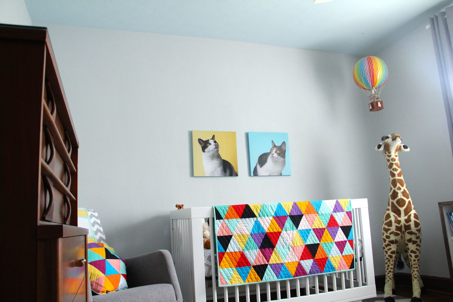Vibrant colors in the ceiling paint and decorations give this nursery a whimsical flair.