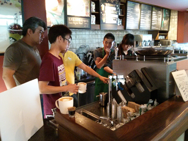 Starbucks barista, food and drink stylists, and client deliberating on how to make the design more perfect.