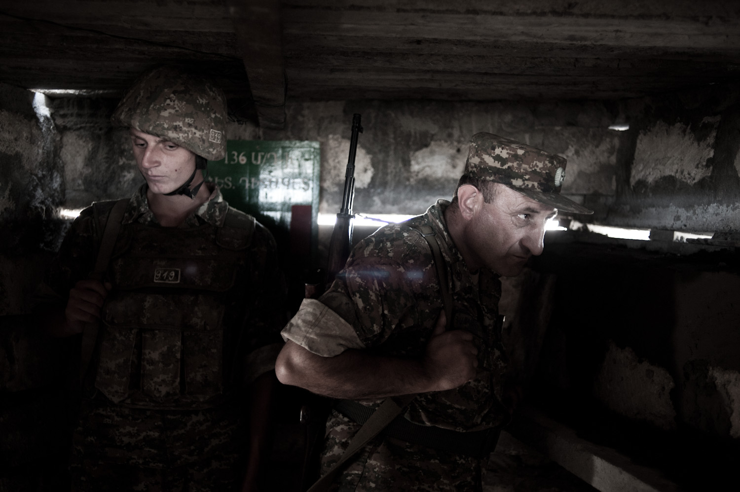 Colonel Alik Sargsyan watches the Azerbaijani frontline located 30 meters from his position at a lookout post, with young conscript Arman in the background.