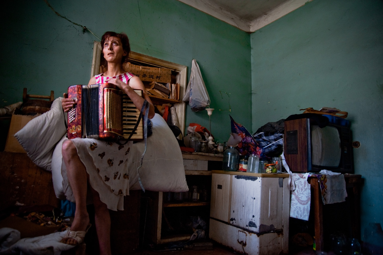 Narine with the accordion she once played as a girl. With her 4 children, she escaped an abusive, alcoholic husband who regularly beat and raped her. The family now lives in this dilapidated house in Arinch village.