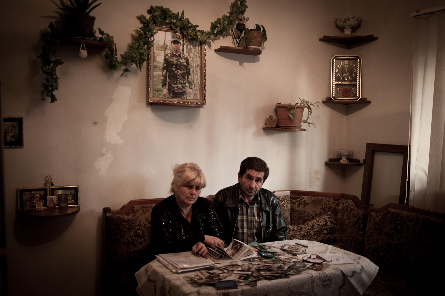 Arthur's parents Smbat and Irina sit beneath their son's portrait sifting through case files, paperwork and autopsy photographs related to their son's death.