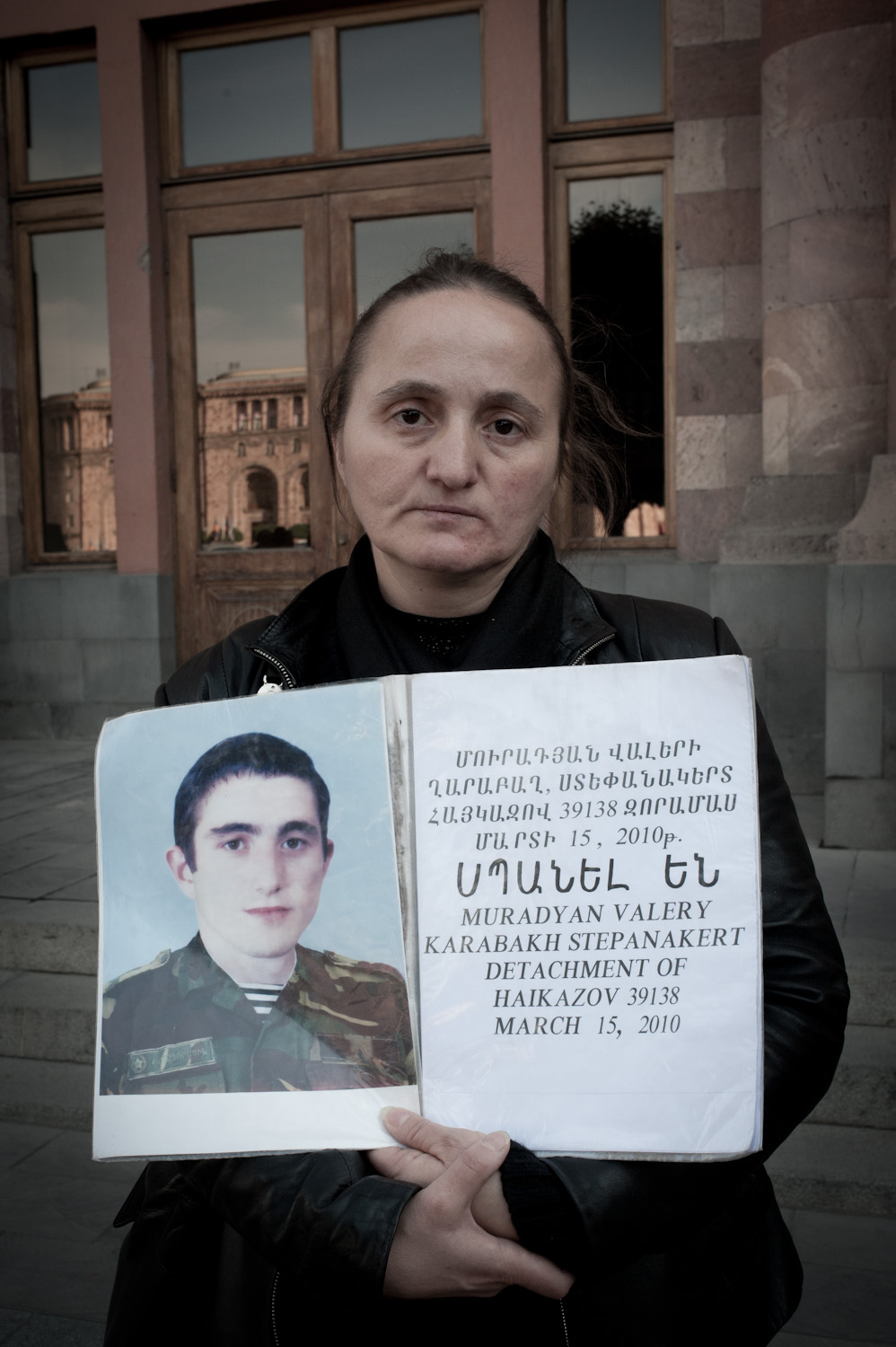 Cradling her deceased son Valery's photograph, Nana Muradyan stands in  front of the government building in Yerevan where she and other mothers  protest the unsolved crimes committed against their sons during their  mandatory military service.