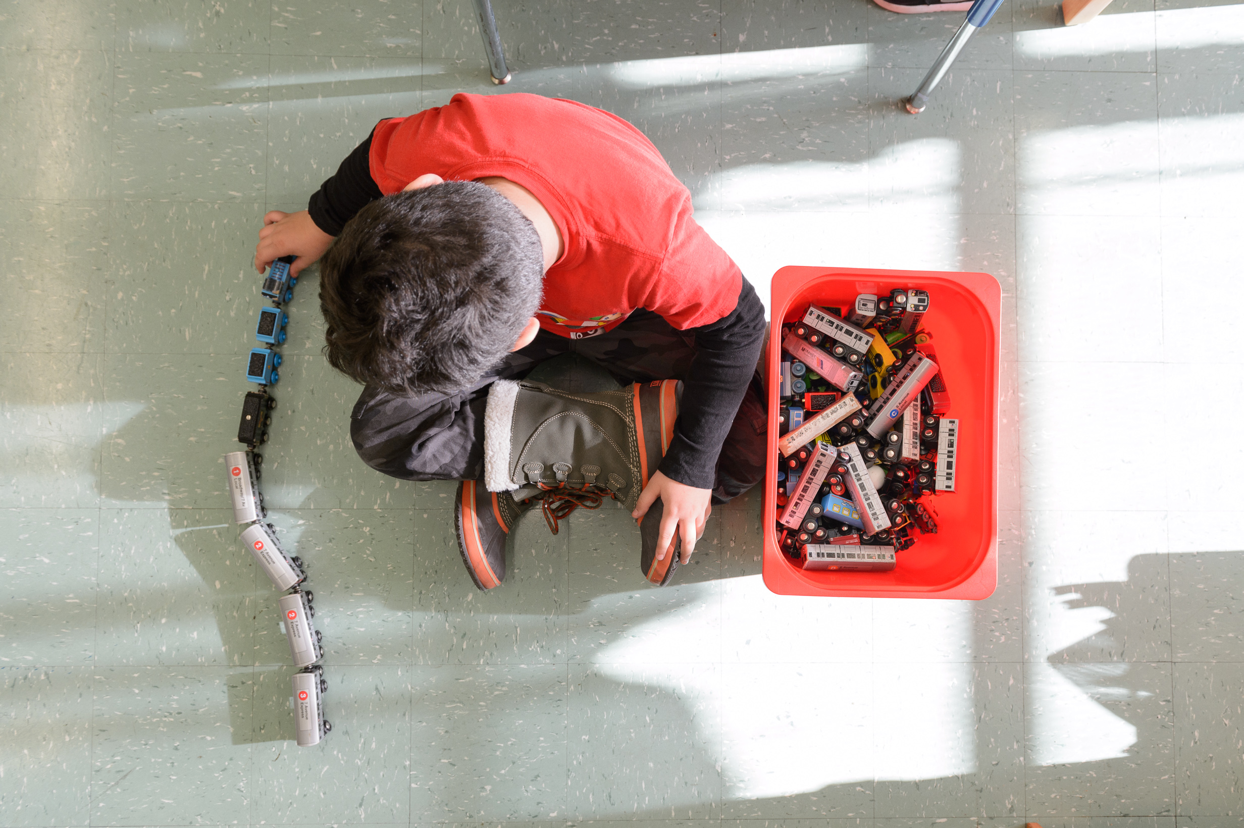 Young boy playing with toy train at after school