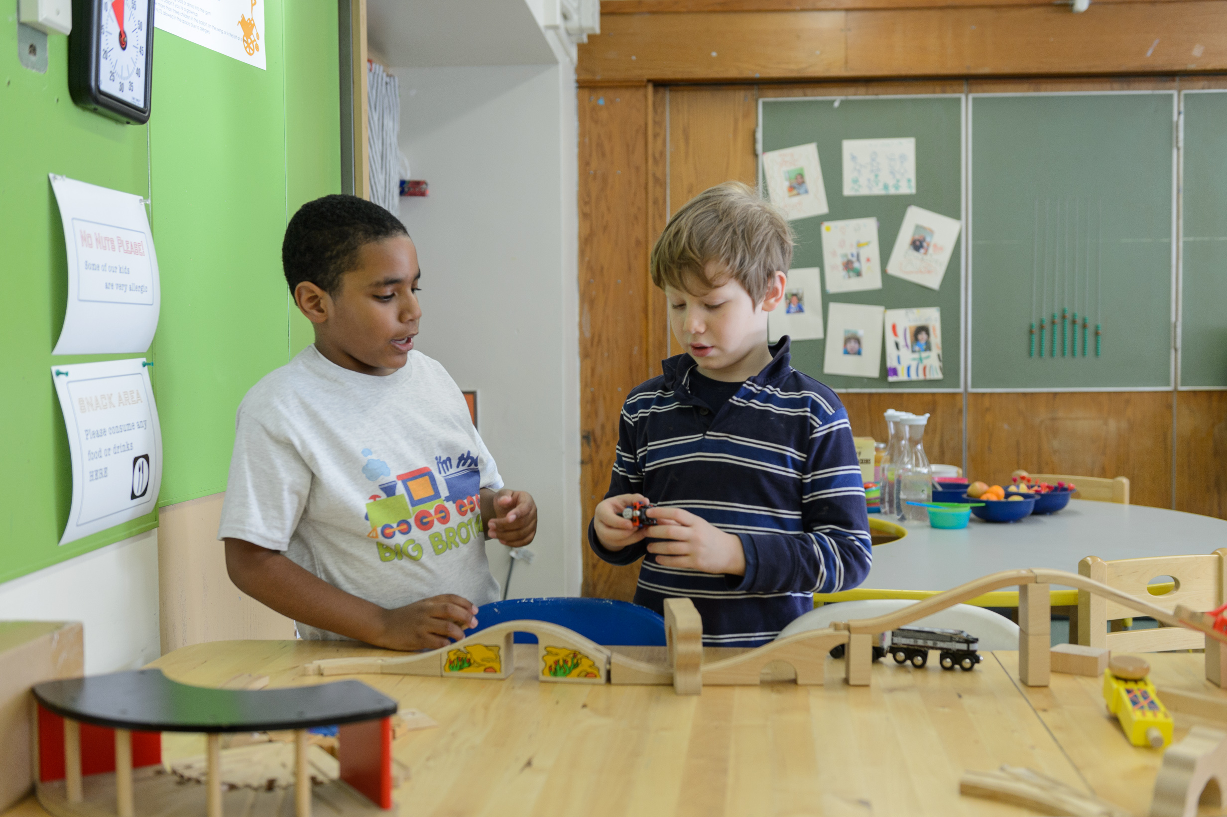 Two young boys playing with wooden toys at after school