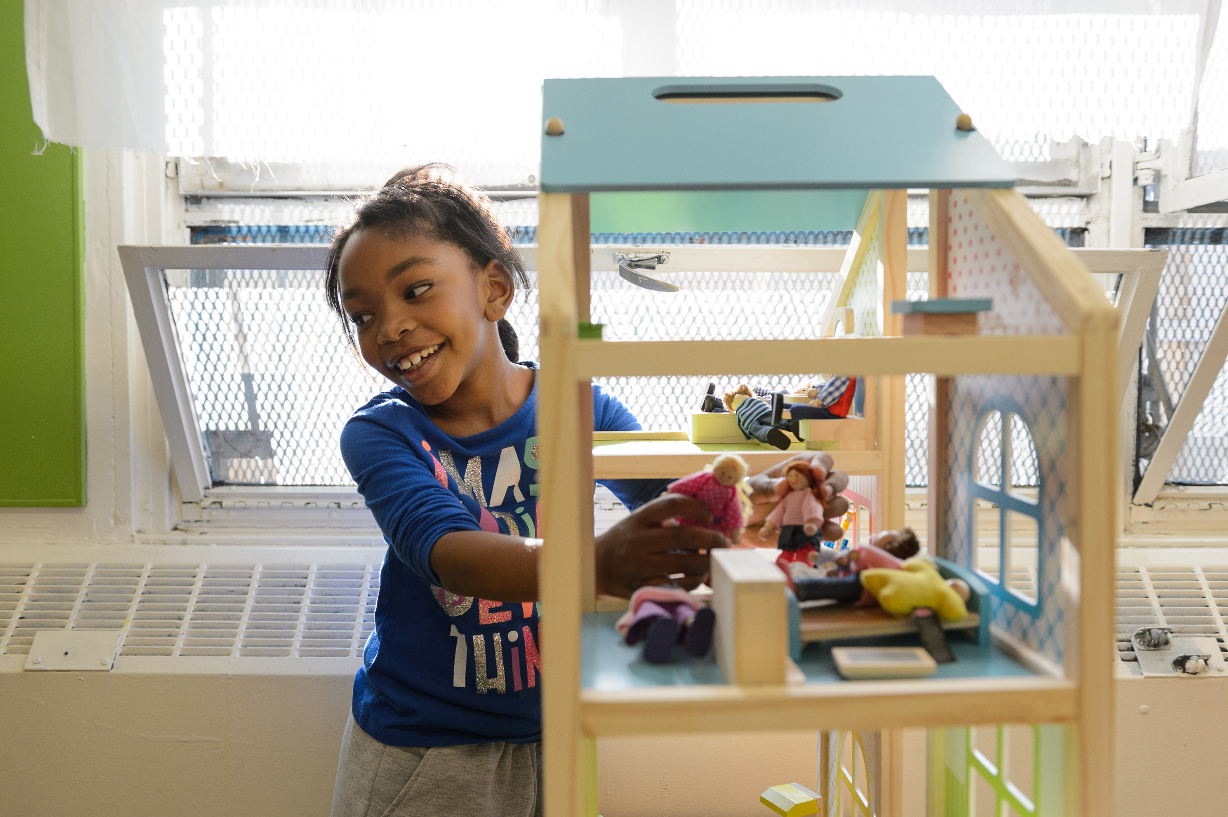 Grace, playing with toy house at after school