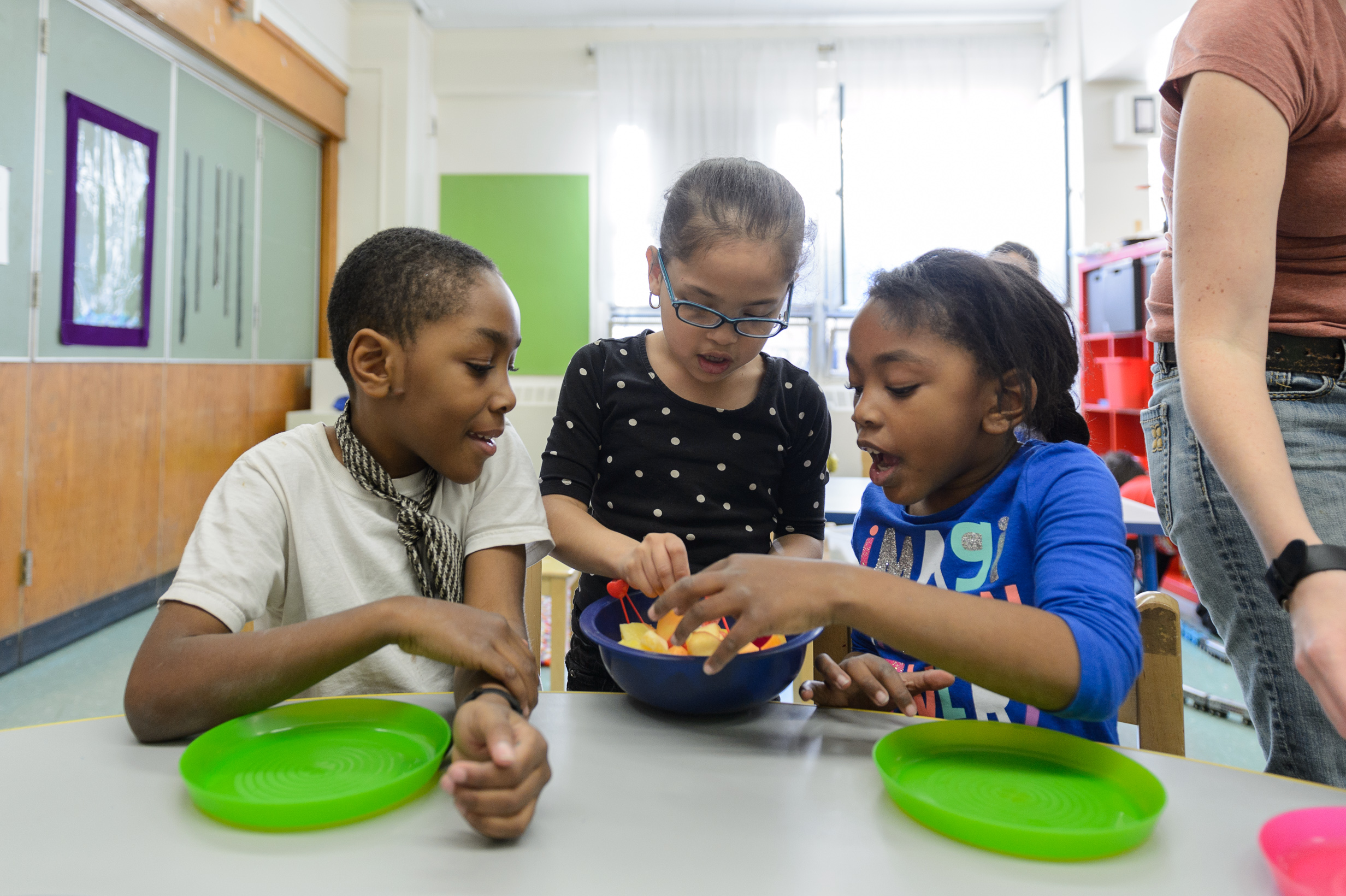 Children making snacks with fruit at after school