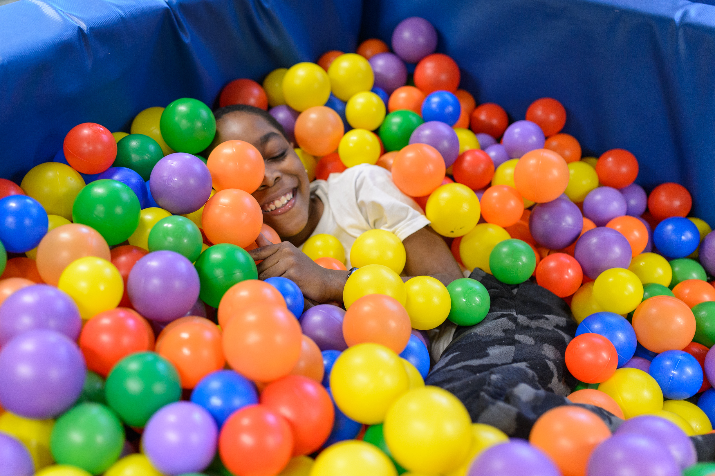Young boy having fun in the ball pit at sensory gym