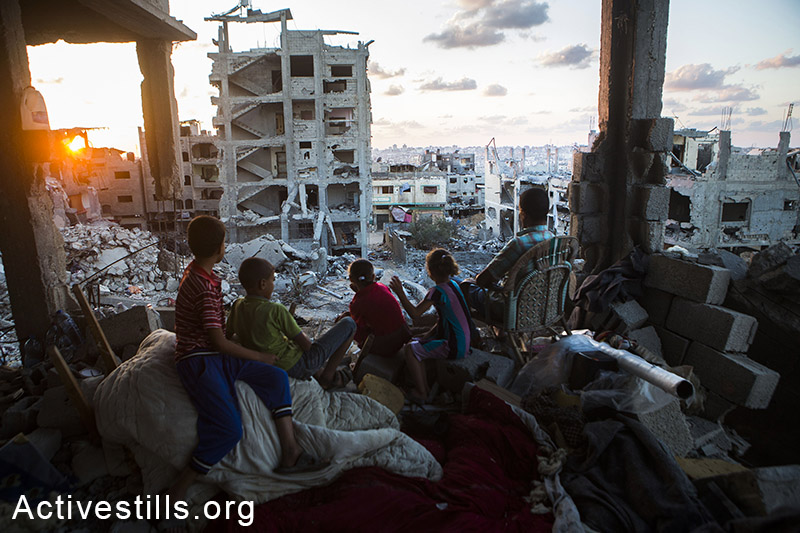 A Palestinian family sits in their destroyed home in a quarter in At-Tuffah district of Gaza city September 21, 2014. (Photo: Anne Paq/Activestills.org)