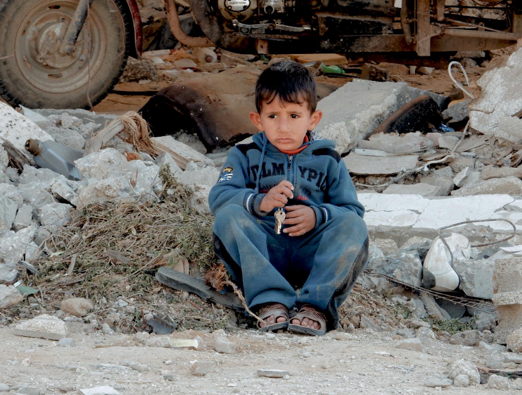 Boy sitting in rubble in eastern Khan Unis in the Gaza Strip     Photo A. Rothchild
