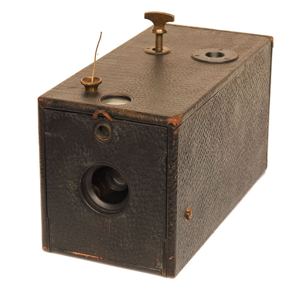 Kodak Box Model 1   1889-1895. Out of such a simple box camera came a giant. The Kodak Model 1 Box camera was the model George Eastman marketed to the public so successfully. It was also his first production model. The camera sold for $25 with 100 exposures of film preloaded and the amateur only needed to point and pull the wire (pre-shutter button). The winding key at the top enabled selfwinding. But the genious lay in the marketing. These cameras could be sent back to Eastman to have the film processed and printed, A camera reload only cost $10. So a happy customer could be a customer for life. This was the begining of a very successful photographic products business known as Eastman Kodak.