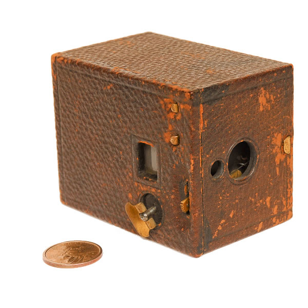 Kodak Model D Camera   1901-1933. This was a cardboard box camera that used 6 exposures of 120 film. 120 film was introduced with this camera. Note the small size of the Kodak Model D box camera as compared to this modern dollar coin. Acquired from Bernie Boston.