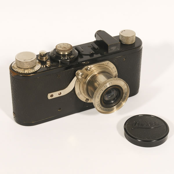 """Leica 1A   1926-1930 The first production model from Leica, these cameras did not have a rangefinder. Also the Elmar F3.5/50mm lens was not interchangeable.  Ernst Leitz began in 1849 making microscopes. It was not until 1913 that they began making cameras. Leitz designer, Oskar Barnrnack, had a personal reason for the size of this camera. He was a hiker who had ashma and could not carry the heavy folding cameras of the time. With the Leitz company's support he pioneered the concept of a """"small negative and an enlarged print"""". He used 35mm movie film that was available at the time creating a relatively small negative which required a smaller body and thus a significantly smaller and lighter body. These first cameras were not successful and were put on the shelf until 1925 when they were reintroduced. From then on Leica has been the name for high quality 35mm cameras."""