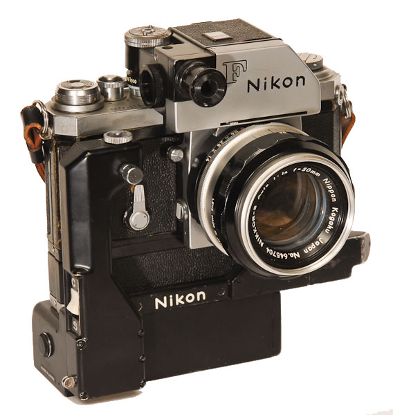 """Nikon F Camera with Motor   1959. Recognized by the round CdS cell on the front of the prism finder. The Photomic CdS meter prism read light directly through the meter, not through the lens. Nikon made 2 motordrives for the F camera. This was the press photographers camera with countless """"war"""" stories about its toughness especially in the coverage of the Vietnam War."""