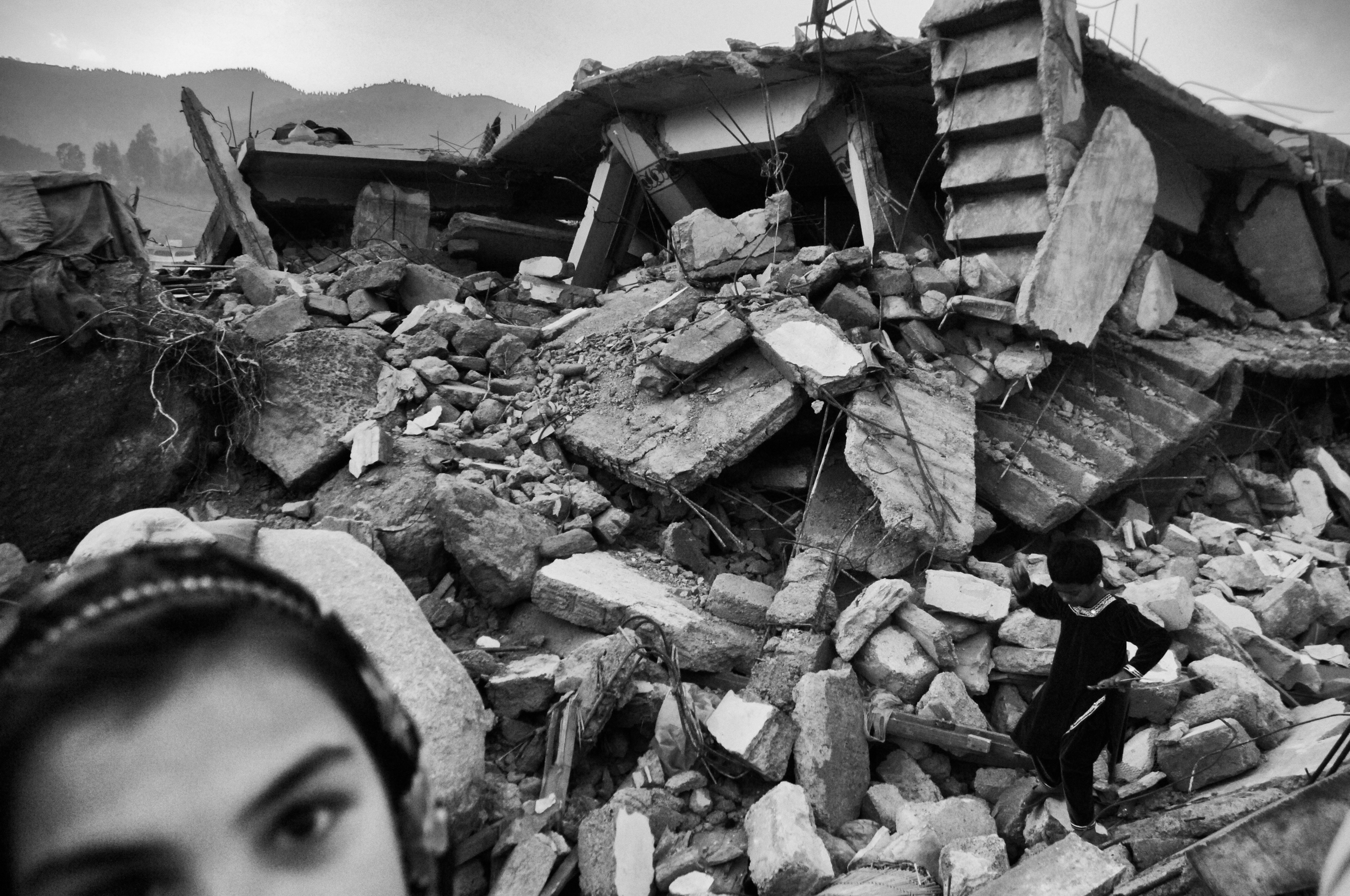 A young girl in the rubble during  Eid  al-Fitr in Balakot, NWFP, Pakistan, November 11, 2005. (Photo / Mark Pearson) The massive October earthquake in Kashmir affected one of the highest and most remote places on earth. Difficult terrain slowed the relief effort and the largest scale humanitarian air operations since the Berlin blockade began.