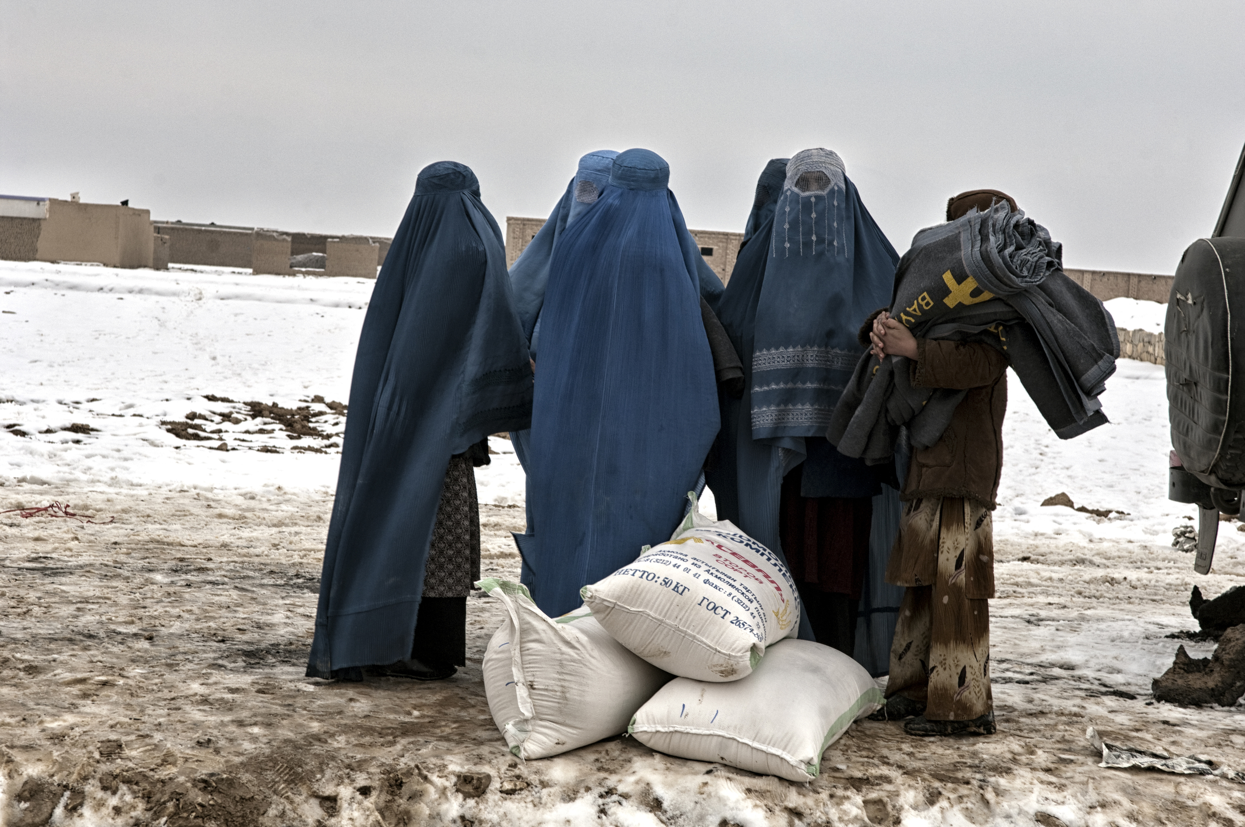 Afghan women collect winterised aid from a distribution point by ACTED in a displacement camp near Pul i Khumri, Baghlan Province, Afghanistan, February 13, 2008. (Photo/Mark Pearson)