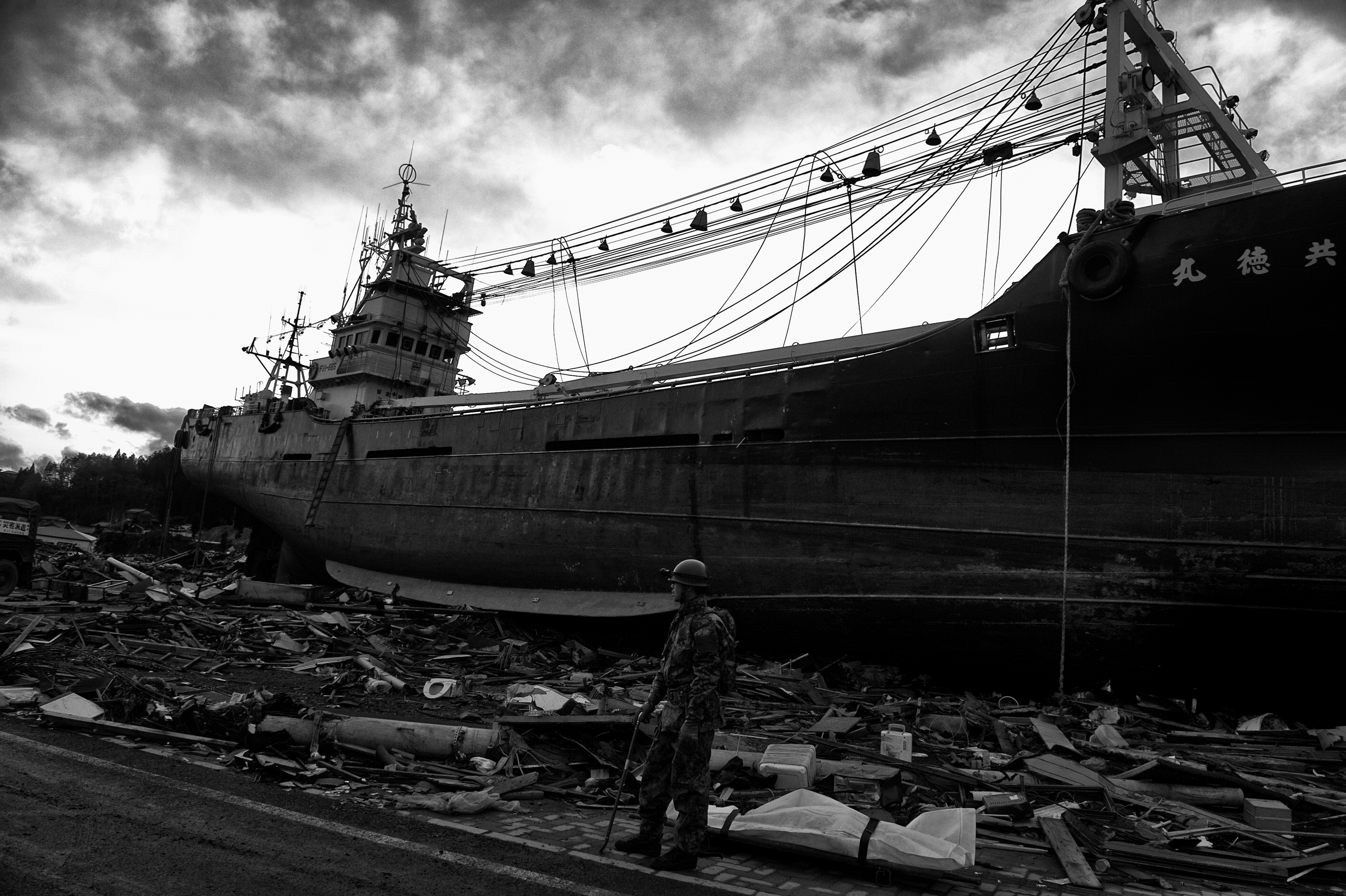 A Japanese soldier puts a casualty next to the   Kyotoku-maru fishing trawler that was swept inland during the tsunami that followed the 2011 Tōhoku earthquake and tsunami in the city of Kesennuma, Miyagi, Japan, March 26, 2011. (Photo/Mark Pearson)