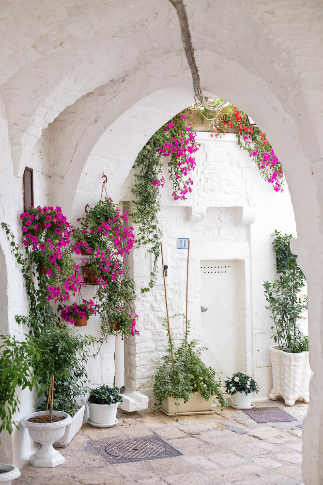 All white everything with a pop of floral color in Cisternino