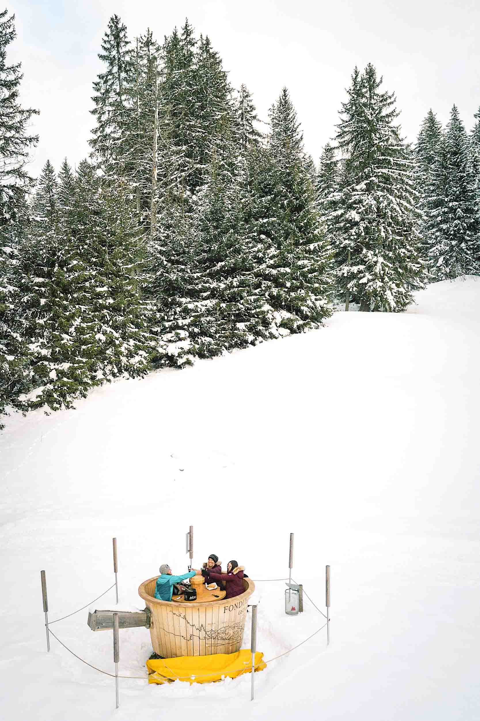 Eating fondue in the Swiss Alps in a large wooden fondue pot