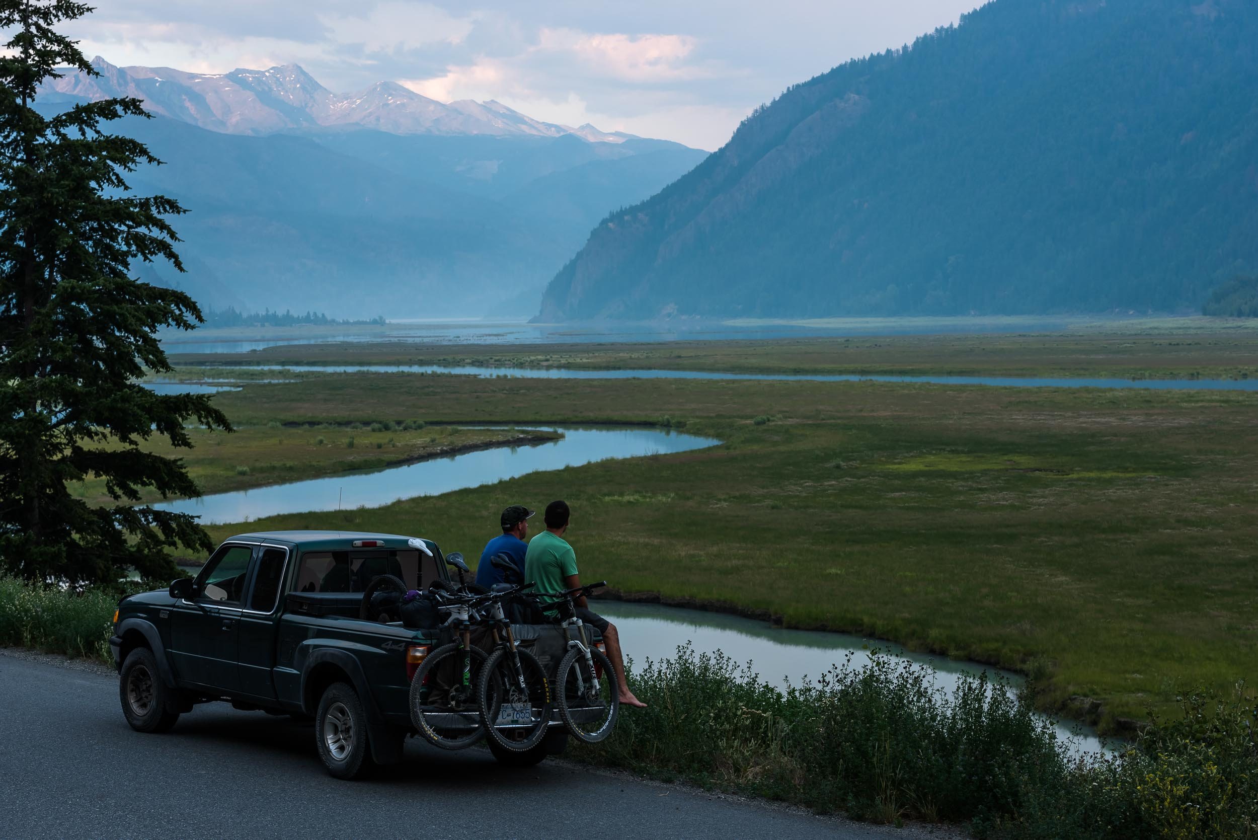 Mountain bikers sitting on a truck on the side of the road near Gold Bridge in the Bridge River Valley. Credit: BC/Reuben Krabbe