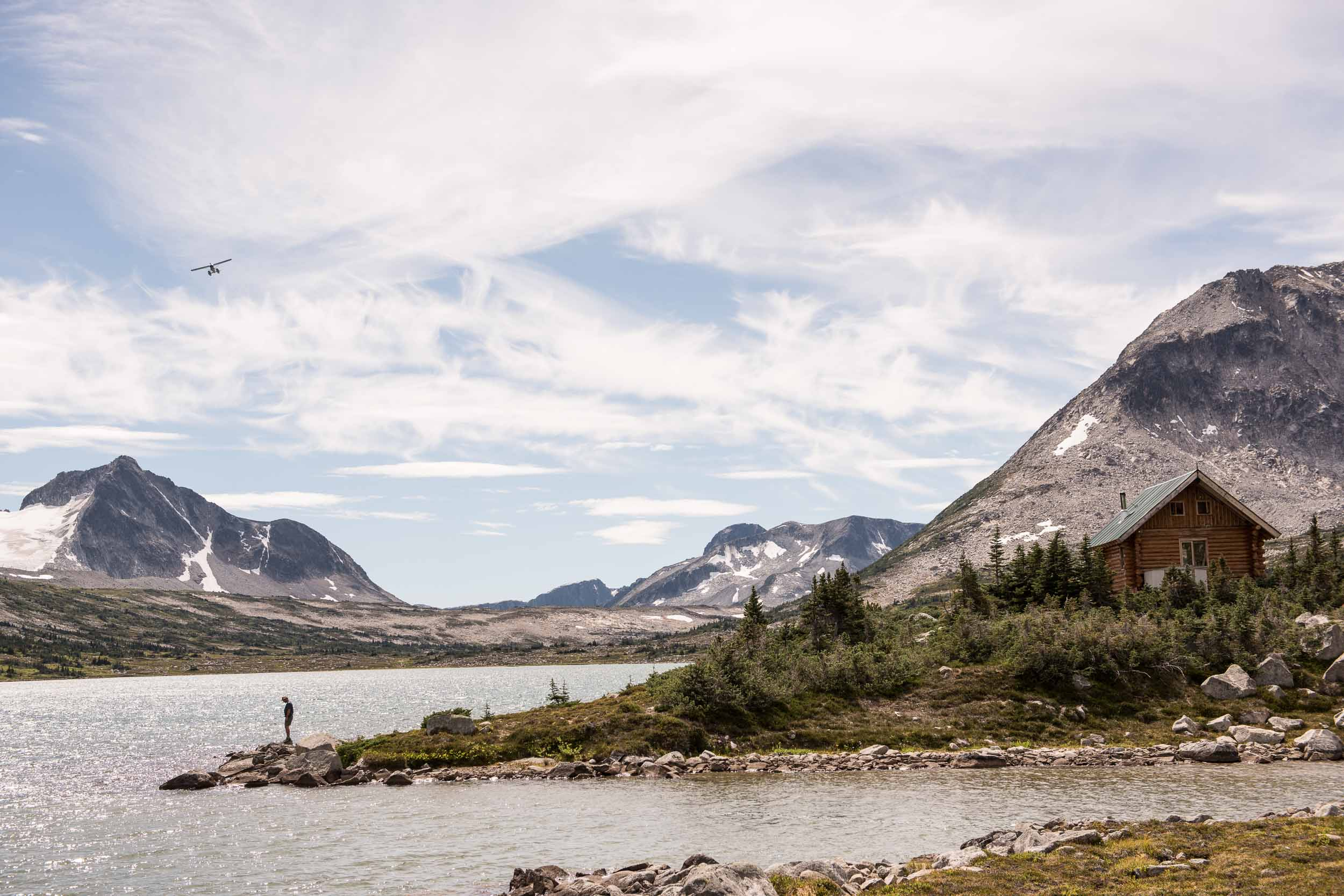 A hiker waiting for a airplane on the shores of Wilderness Lake. Credit: Destination BC/Kari Medig