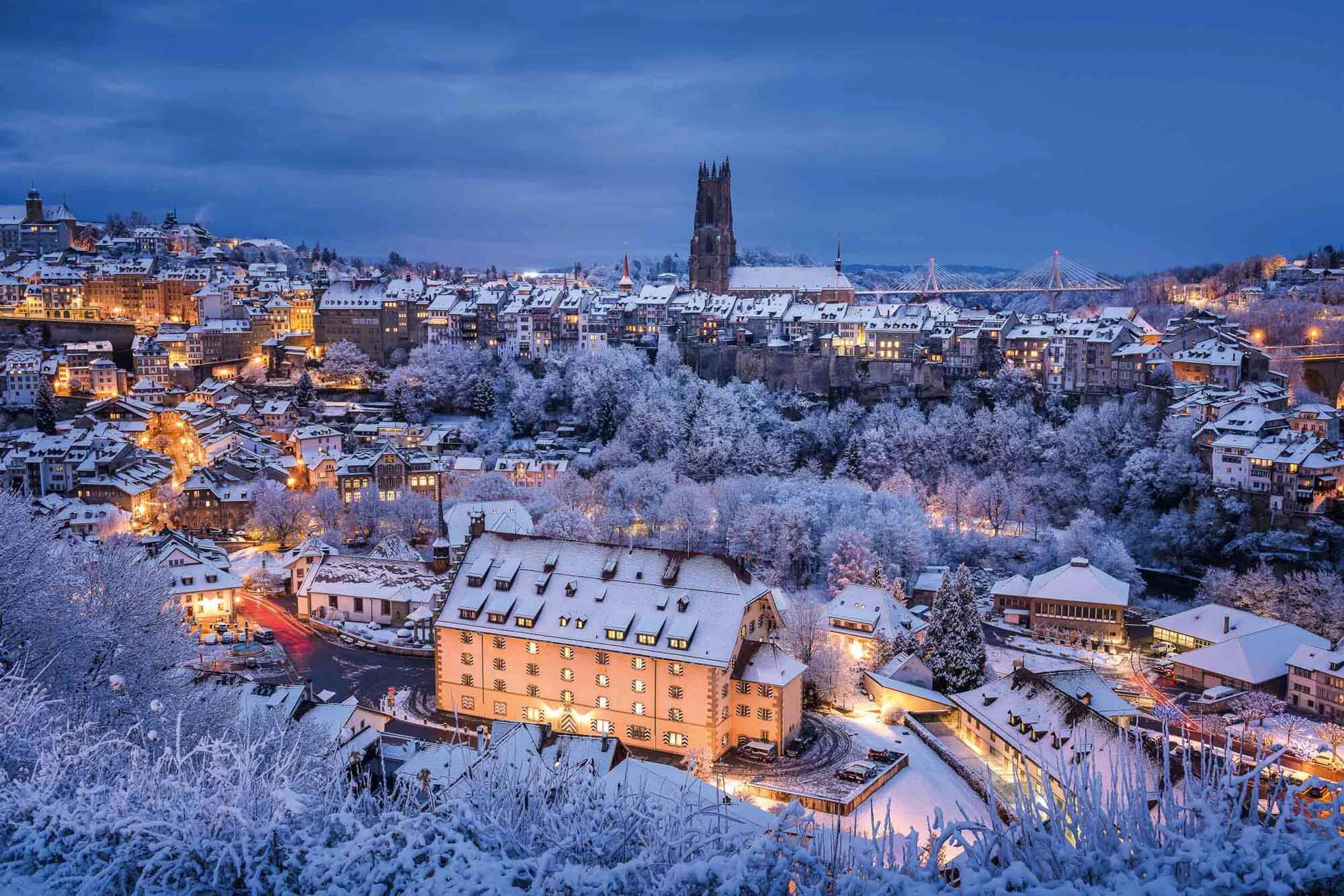 Daybreak with winter panorama in Friborg with the cathedral and the Poyabruecke in the background. Copyright by: Switzerland Tourism