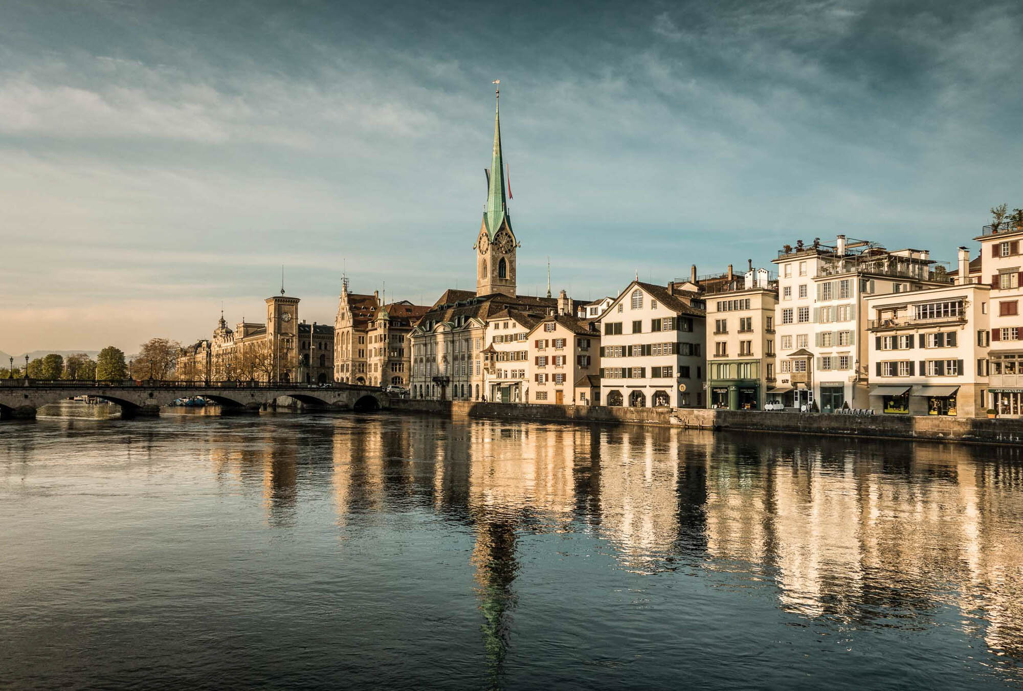 Morning mood at the Limmat overlooking the Fraumuenster, townhouse and Muensterbruecke, Zurich. Copyright by: Switzerland Tourism