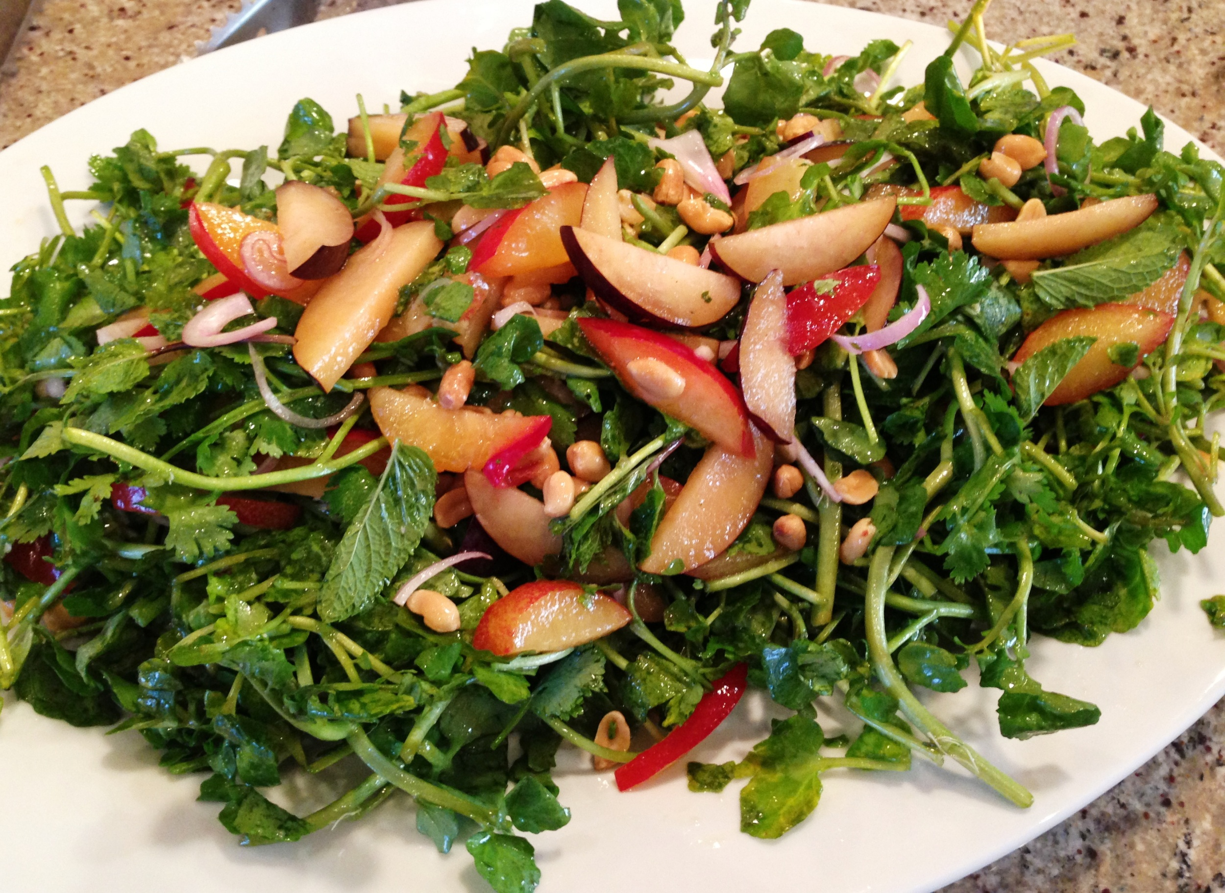 Watercress and herb salad with stone fruit, red onion, peanuts, and Vietnamese nuoc mam vinaigrette
