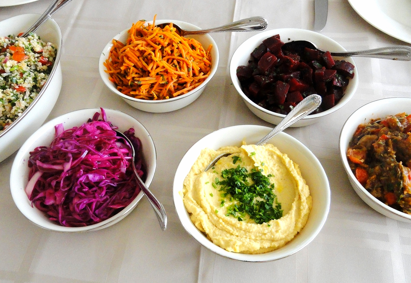 Israeli salads: vegetable Israeli couscous, red cabbage, carrot-cumin, hummus, Moroccan spiced beets, roasted eggplant and tomato with za'atar