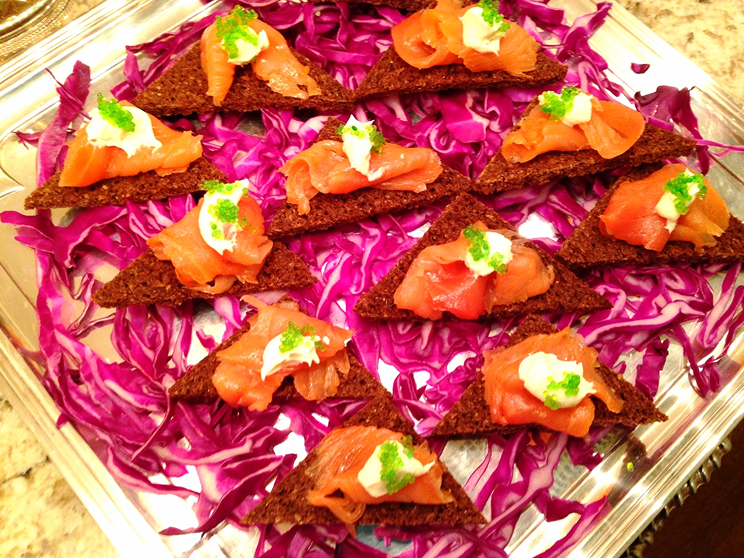 Home-cured gravlax with horseradish cream and wasabi caviar on pumpernickel toast point