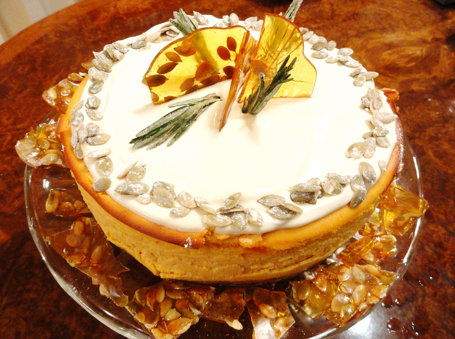 Pumpkin cheesecake, sweetened sour cream topping, sugared pepitas and rosemary, pumpkin seed brittle