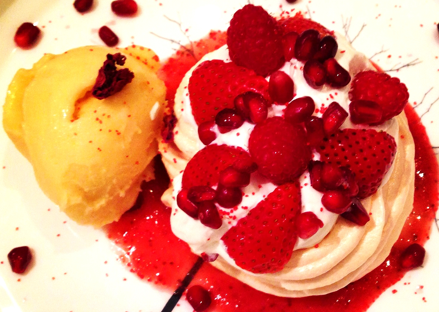 Mini Pavlova with creme chantilly, red fruits, strawberry sauce, and passion fruit sorbet