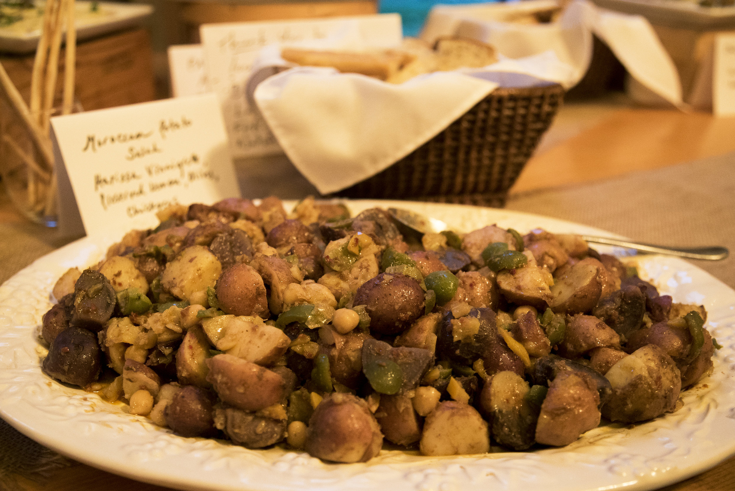 Moroccan potato salad with harissa vinaigrette, green olives, chickpeas, preserved lemon, sumac, parsley