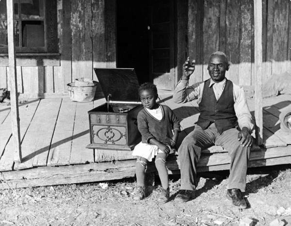 Sharecropper Lonnie Fair and his daughter listening to a Victrola on their front porch (Mississippi, USA) by Alfred Eisenstaedt, 1937
