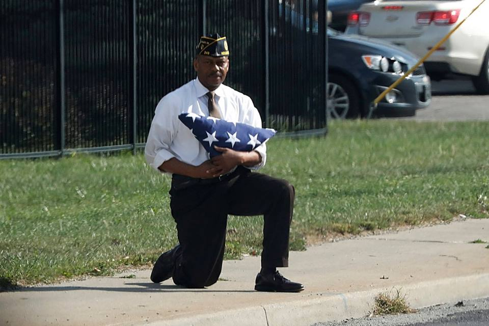 A man kneels woth a folded U.S. flag as the POTUS motorcade passes him in Indianapolis by Jonathan Ernst, 2017