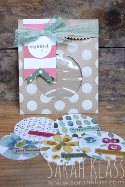 A    Circle Framelit    cuts a neat window out of this bag, and a    cellophane bag    inside holds simple gift tags punched from the    English Garden Designer Series Paper   . The spotty mask from the    Dots and Stripes    pack, along with    Whisper White craft ink    adds some fun decoration